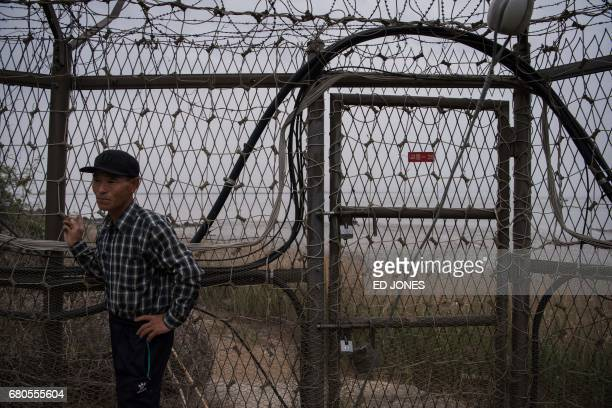 TOPSHOT Farmer InSuk Hwang stands outside his home next to the fence of the Demilitarized Zone on Gyodong a tiny outlying island near to the west of...