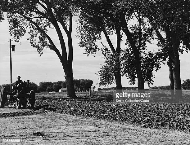 A farmer is seen plowing ground to prepare a garden a contrast can be seen between the hard unturned ground and the soil that has been turned a house...