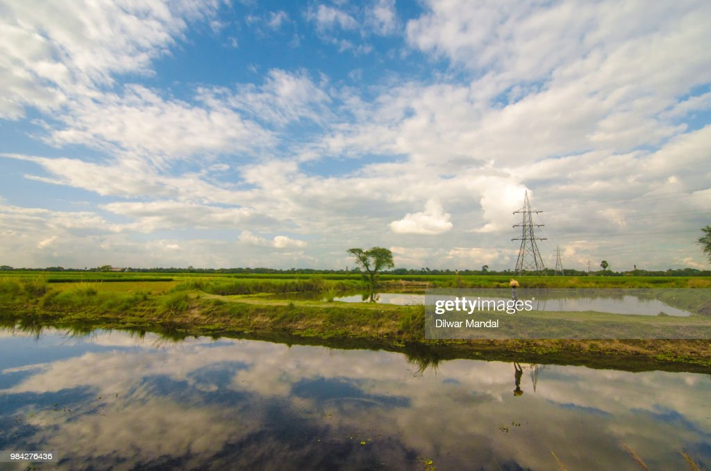 A farmer is walking behind a small lake in a village : Stockfoto