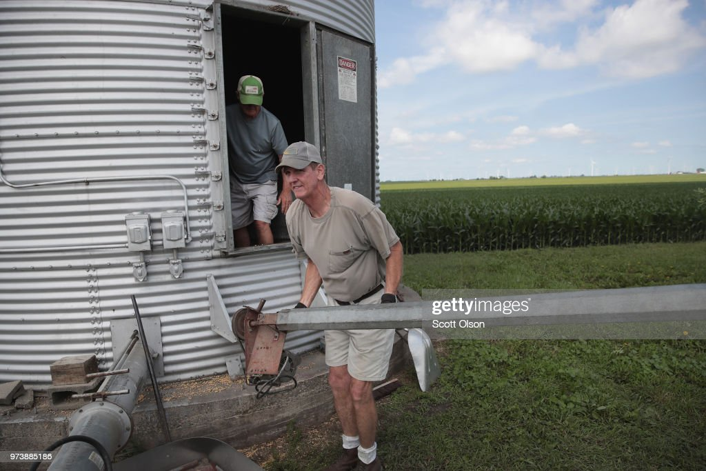 Farmer John Duffy (L) and Roger Murphy load soybeans from a grain bin onto a truck before taking them to a grain elevator on June 13, 2018 in Dwight, Illinois. U.S. soybean futures plunged today with renewed fears that China could hit U.S. soybeans with retaliatory tariffs if the Trump administration follows through with threatened tariffs on Chinese goods.