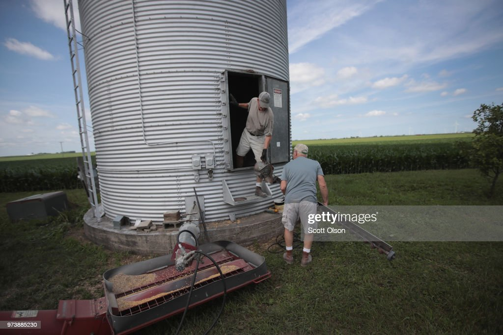 Farmer John Duffy (R) and Roger Murphy load soybeans from a grain bin onto a truck before taking them to a grain elevator on June 13, 2018 in Dwight, Illinois. U.S. soybean futures plunged today with renewed fears that China could hit U.S. soybeans with retaliatory tariffs if the Trump administration follows through with threatened tariffs on Chinese goods.