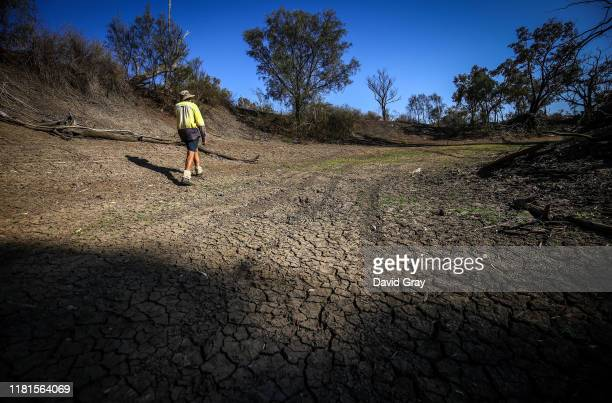 Farmer Johnnie McKeown walks in the dried-up bed of the Namoi River located on the outskirts of his drought-affected property, near the north-western...