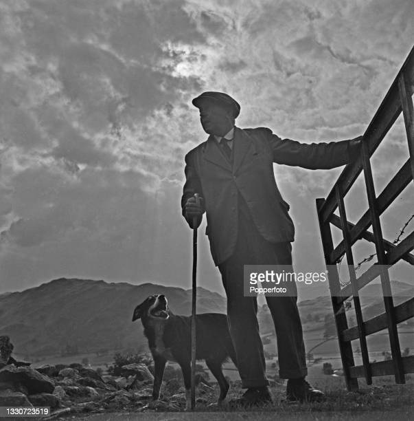 Farmer Joseph Relph and his sheepdog Moss return home from the fields at the end of a day tending to a flock of sheep on his farm at Threlkeld, near...