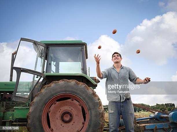 Farmer juggling with freshly harvested organic potatoes
