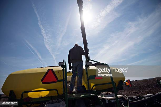 Farmer Kent Bickett loads seed corn into a Deere Co John Deere 24row planter during planting in Malden Illinois US on Tuesday May 6 2014 This year's...