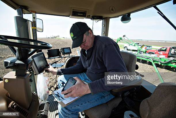 Farmer Kent Bickett loads seed variety codes into a computer on a Deere Co John Deere tractor pulling a 24row planter in Malden Illinois US on...