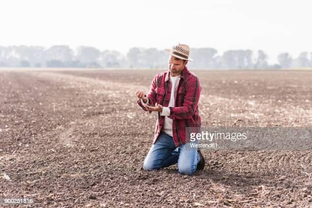 Farmer kneeling on plowed field examining soil