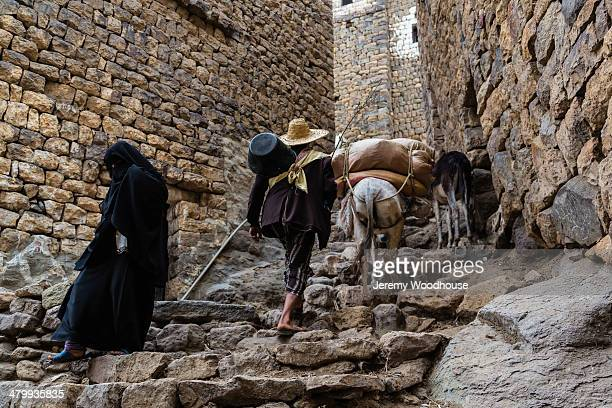 farmer leading donkey up steps into town - sanaa stock-fotos und bilder