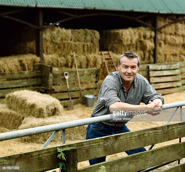 Farmer Leaning on a Gate, With a Barn and Bales of Hay