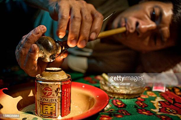 A farmer lighting his pipe of opium after a hard day of work on their tea plantations in a mountain village of Shan state It has long been known that...