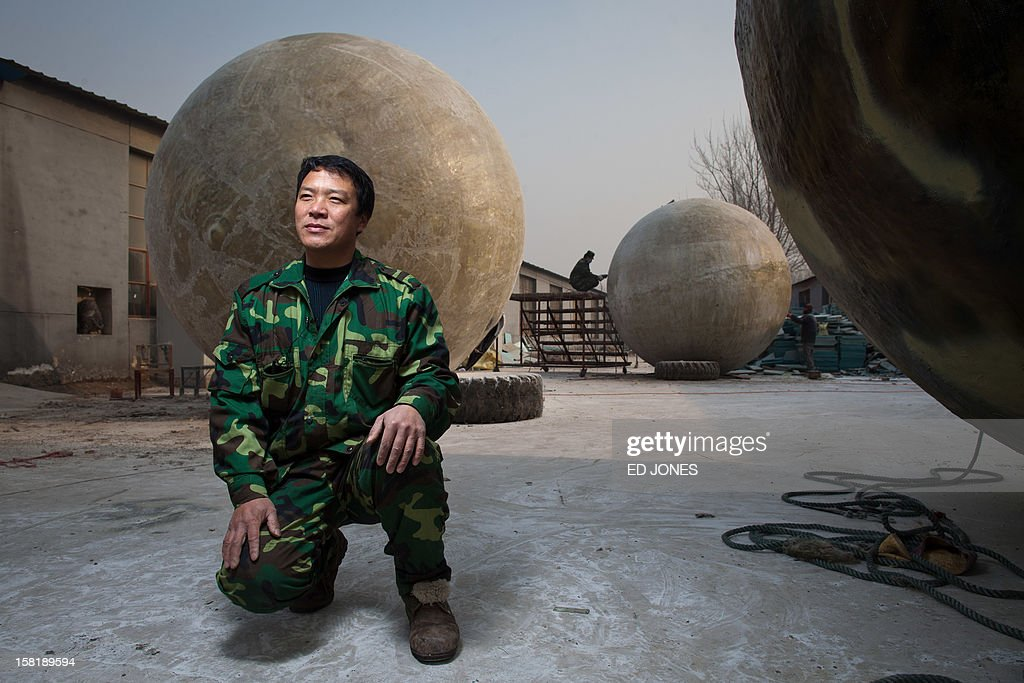 Farmer Liu Qiyuan poses among survival pods that he built and has also dubbed 'Noah's Arc', in a yard at his home in the village of Qiantun, Hebei province, south of Beijing on December 11, 2012