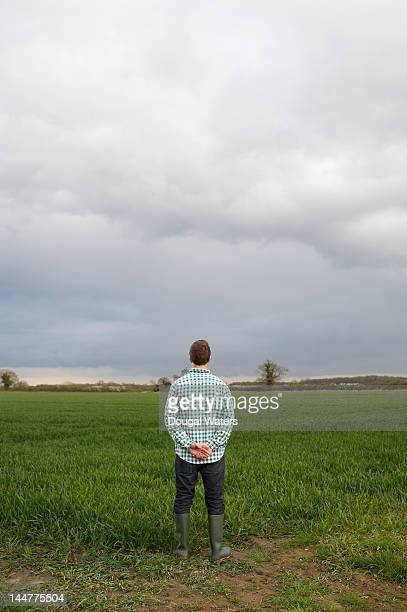Farmer looking out across land.