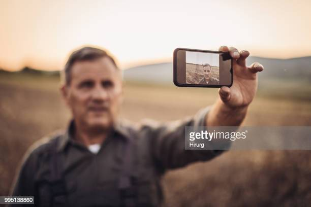 Agriculteur faisant selfie dans déposée de blé