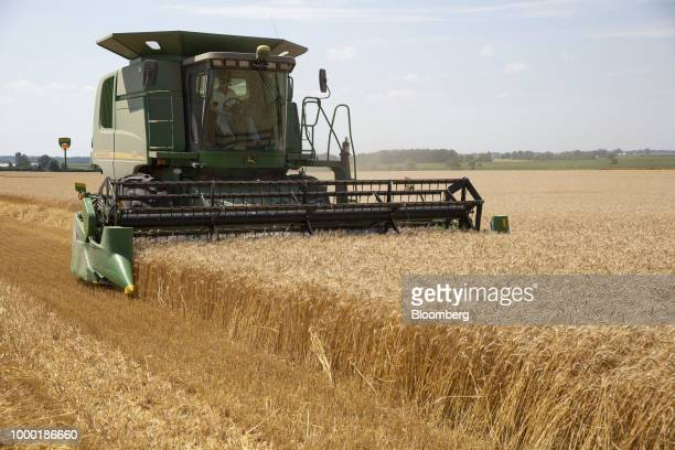 A farmer operates a Deere Co John Deere 9560 combine harvester during a soft red winter wheat harvest in the village of Kirkland in Dekalb Illinois...