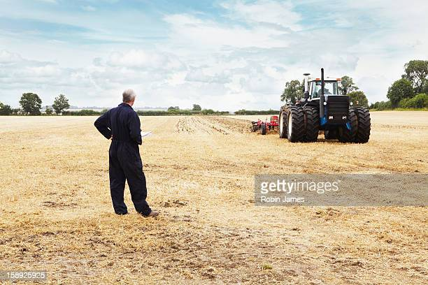 Farmer overlooking tractor in crop field