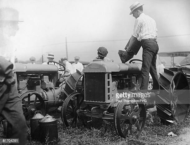 A farmer pours kerosene into a tractor since it is cheaper than gasoline circa 1925