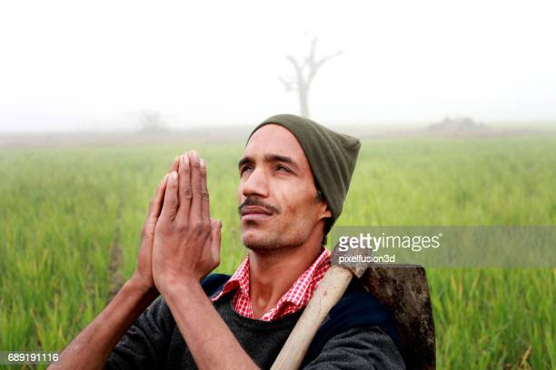 Farmer praying to god for good wheat crop