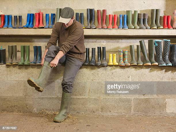 farmer putting on wellington boots - rubber boot stock pictures, royalty-free photos & images