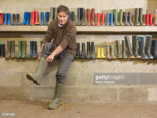 farmer putting on wellington boots - getting dressed stock pictures, royalty-free photos & images