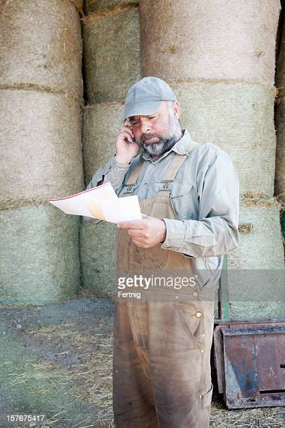 Farmer reading his mail and on a cell phone