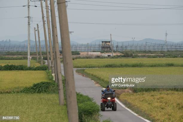 A farmer rides a quadbike before a South Korean military guard post and the skyline of North Korea at the Demilitarized zone separating the two...