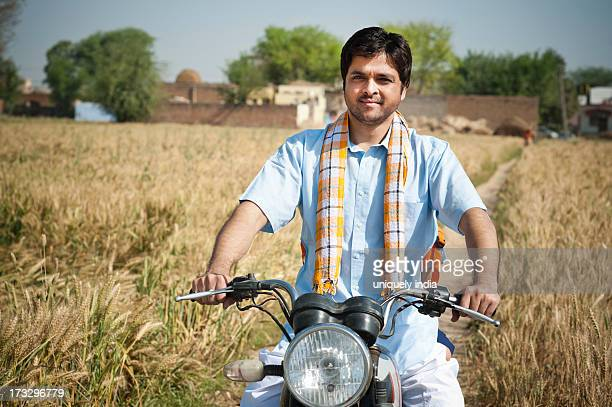 Farmer riding a motorcycle in the field, Sohna, Haryana, India
