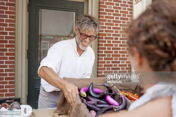 farmer selling organic aubergines on stall - heshphoto stock pictures, royalty-free photos & images