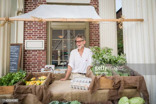 farmer selling organic eggs and vegetables on stall outside store - heshphoto stock pictures, royalty-free photos & images