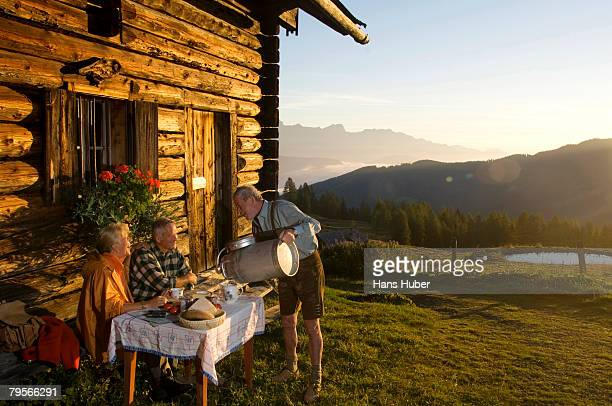 'Mature couple sitting in front of alpine hut, farmer serving them'