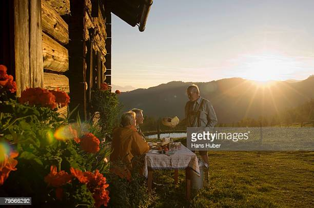 farmer serving mature couple sitting in front of alpine hut - hut stock pictures, royalty-free photos & images