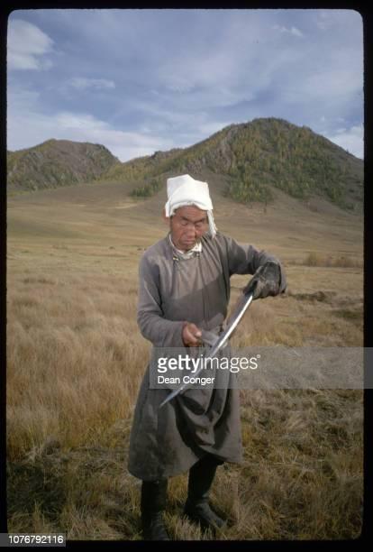 Farmer Sharpening Hay Scythe in Mongolia