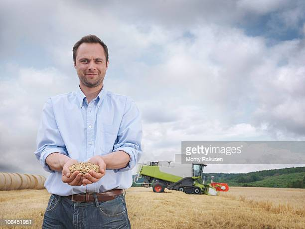 farmer showing a handful of grain - handful stock pictures, royalty-free photos & images