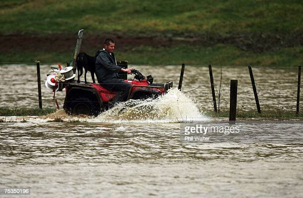 Farmer Simon Donelley and his dog Tam drive a quadbike though floodwater on their farm near Hikurangi July 112007 in Northland New Zealand The top of...
