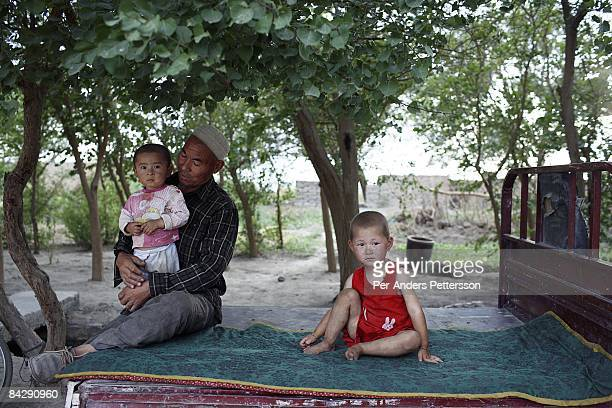 A farmer sits on a flat bed truck with his sons in the shade on June 9 in Turpan China Turpan is famous for its vine production and farming