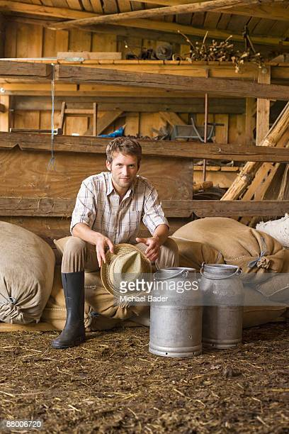 Farmer sitting in barn with milk cans, portrait