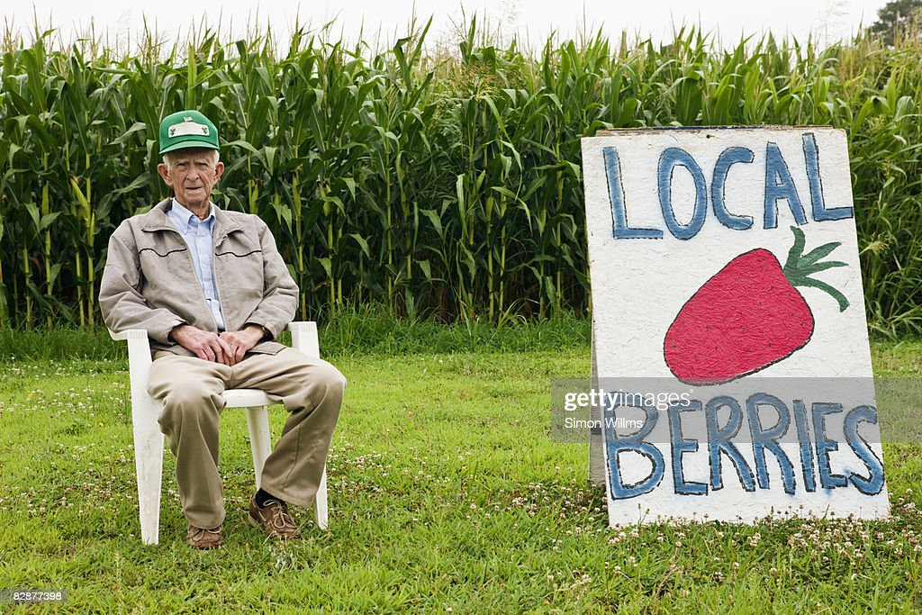 Farmer sitting in front of corn field : Stock Photo