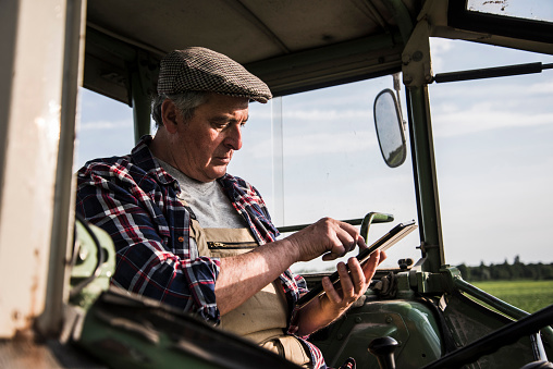 Farmer sitting in tractor using digital tablet - gettyimageskorea