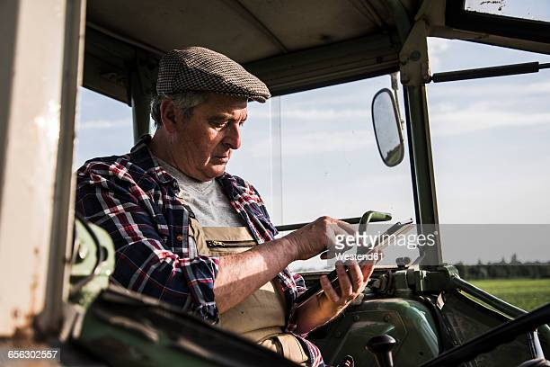 Farmer sitting in tractor using digital tablet