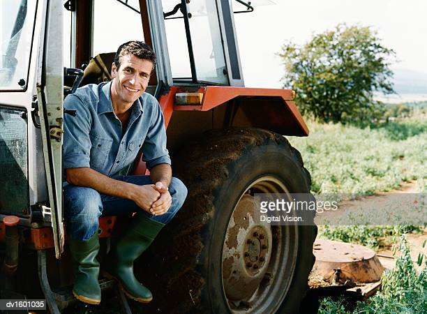 farmer sitting on a tractor in a field - tractor stock pictures, royalty-free photos & images