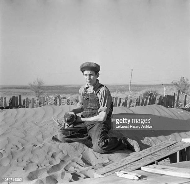 Farmer Son Playing on Soil Drift that Threatens to cover up his Home Liberal Kansas USA Arthur Rothstein Farm Security Administration March 1936