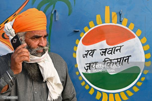 "Farmer speaks on a mobile phone next to a slogan painted on a vehicle that reads ""Hail the Soldier, Hail the Farmer"" during a protest against the..."