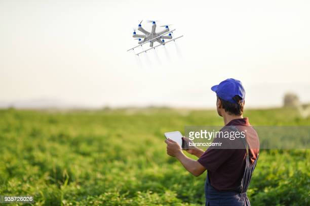 farmer spraying his crops using a drone - drone stock pictures, royalty-free photos & images