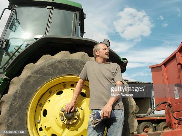 Farmer standing beside tractor, low angle view