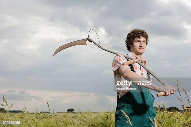 Farmer standing in a field with a scythe