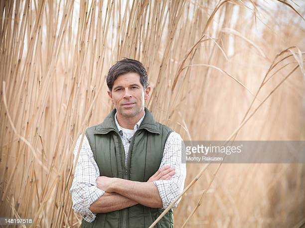 Farmer standing in field of Miscanthus crop to be used for biofuel