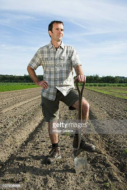 farmer standing in field - main sur la hanche photos et images de collection