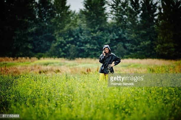 Farmer standing in field talking on smartphone