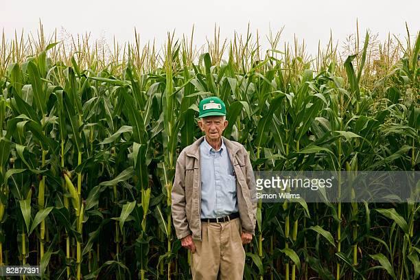 Farmer standing in front corn field