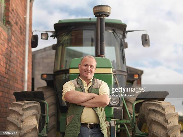 farmer standing in front of tractor - tractor stock pictures, royalty-free photos & images