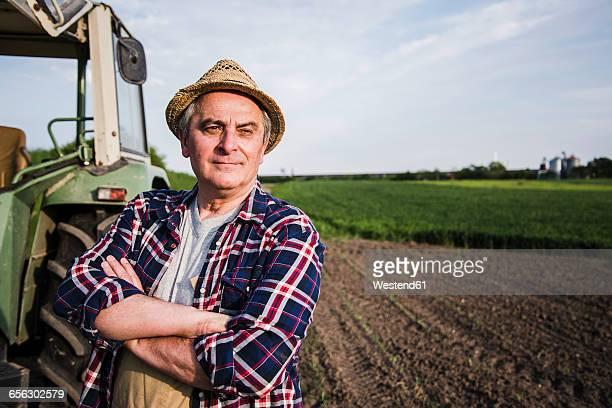 farmer standing next to tractor at a field - bauernberuf stock-fotos und bilder